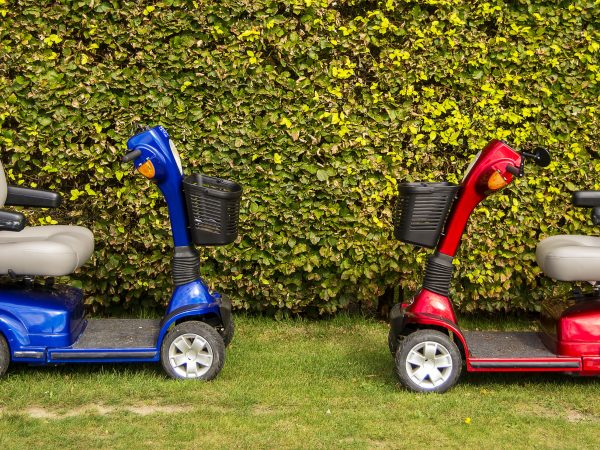 A red and blue mobility scooters on the grass.