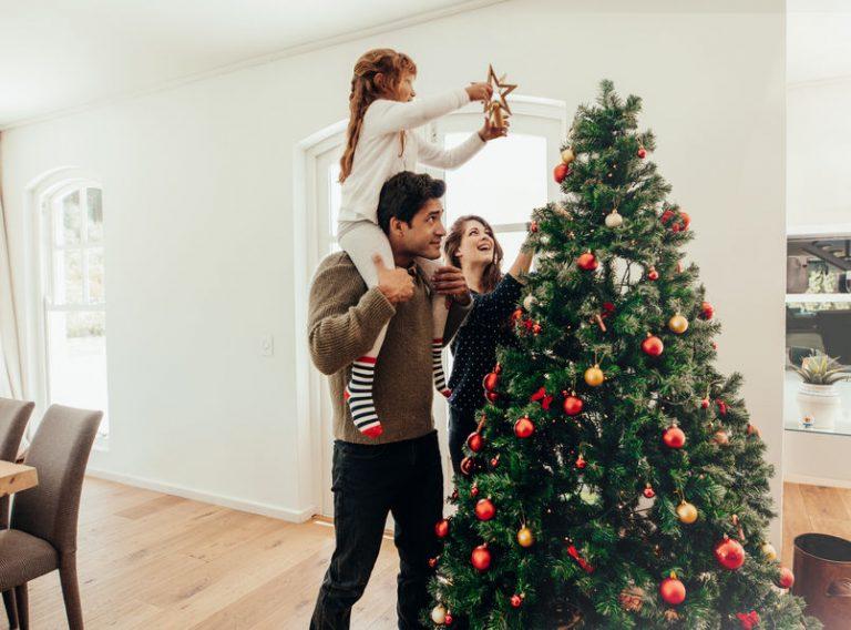 Familia adornando árbol de navidad