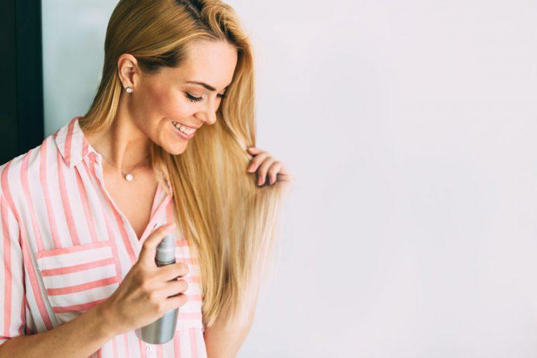 Mujer de cabello claro aplicándose champú seco