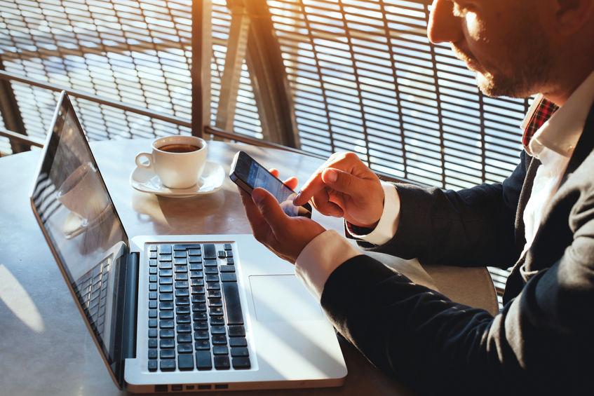 Hombre de negocios utilizando internet en teléfonos inteligentes y portátiles