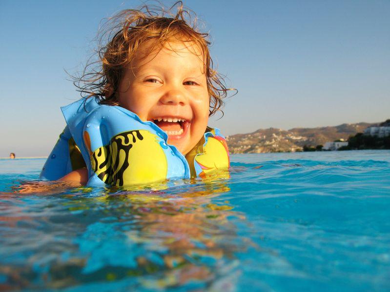 niña en el mar con flotadores