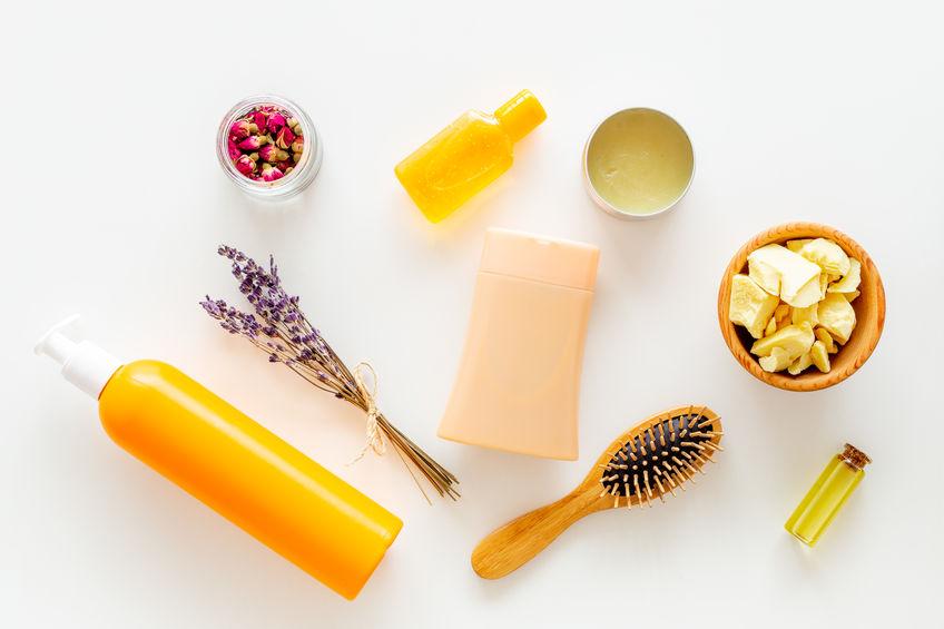 Cosméticos para el cuidado del cabello con jojoba, argán o aceite de coco. Botellas y trozos de aceite en la vista superior de fondo blanco