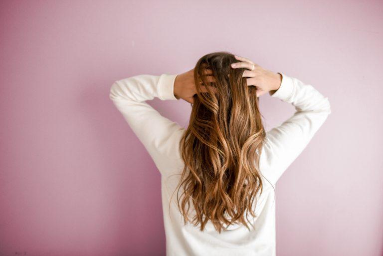 Imagen de mujer de espaldas tocandose el cabello en fondo violeta