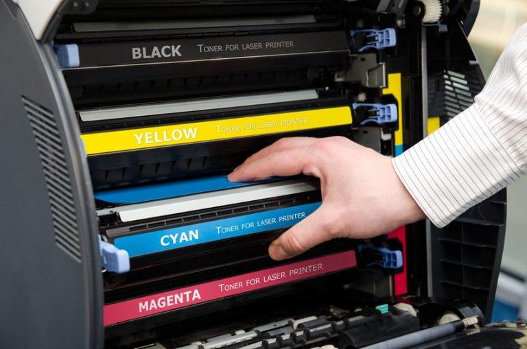 Hombre colocando tinta sobre impresora moderna