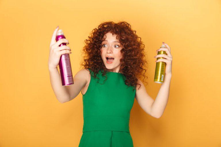 Pelirroja de pelo rizado con dos spray de shampu seco en fondo naranja