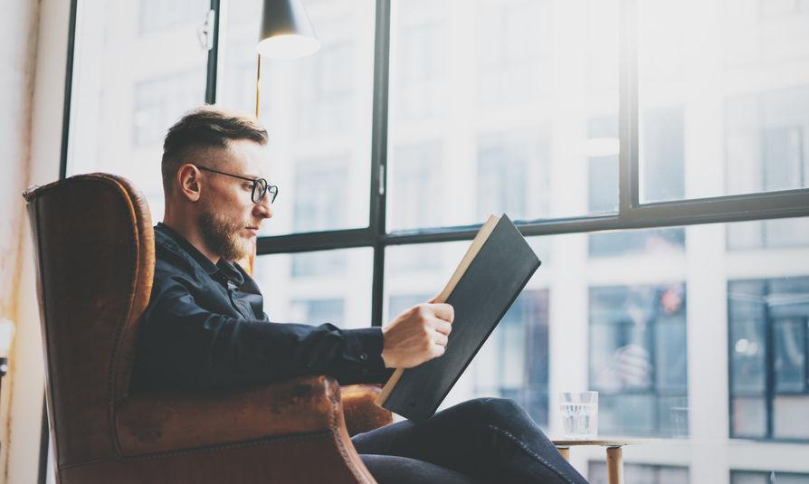 Un hombre leyendo en una butaca