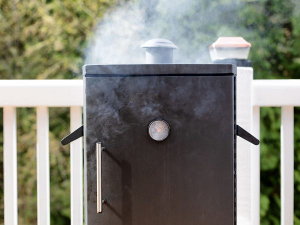 Close up of a cooking smoker with woods in background