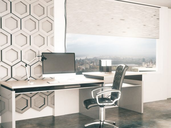 Side view of creative office desktop with honeycomb pattern on wall in the background and window with city view. 3D Rendering