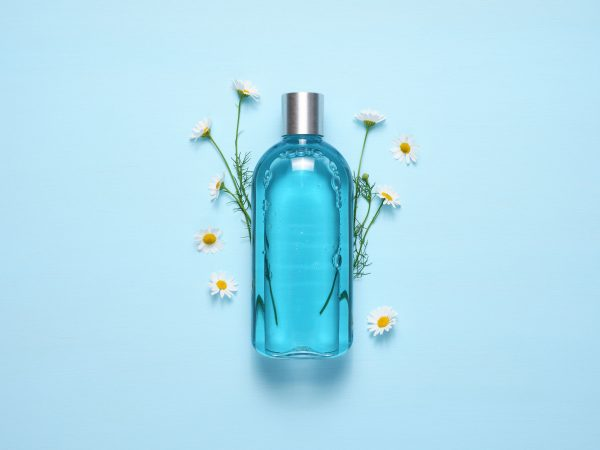 Cosmetic bottle and chamomile flowers on blue table top view
