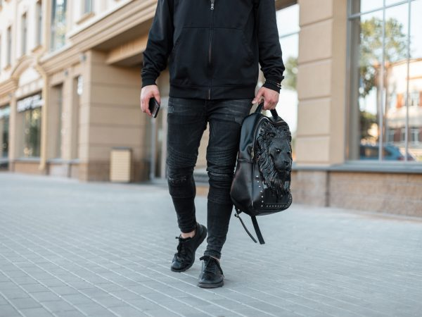 Stylish young man in a trendy black sweatshirt with a leather black backpack with a lion pattern in jeans walks down the street in the city. New collection of fashionable men's clothing. Close-up.