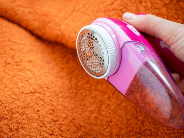 Clothes care. Lint shaver or fabric shaver or fuzz remover in female hand. Woman removing lint on orange wool coat with handheld electric defuzzer