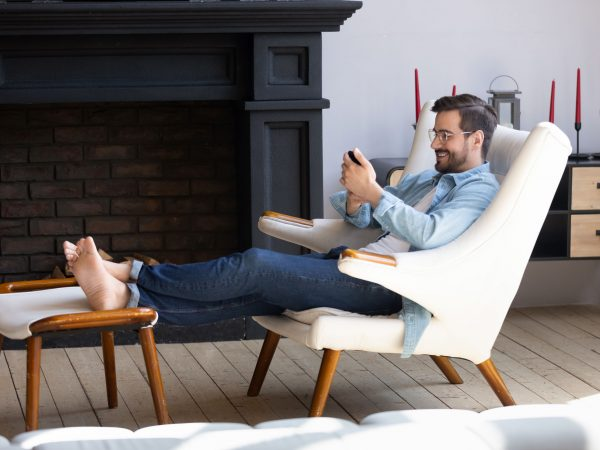 Full length happy young man in eyeglasses relaxing on comfortable armchair, putting legs on ottoman, using smartphone. Smiling millennial guy resting in modern living room, chatting in social network.
