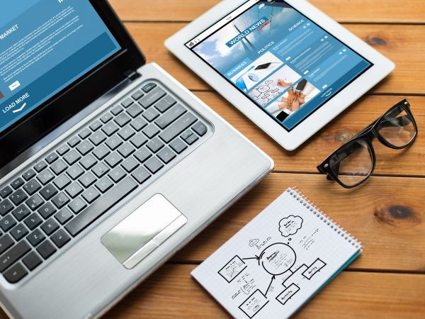 business, responsive design and technology concept – close up of on laptop computer, tablet pc, notebook and eyeglasses with world news and scheme on wooden table
