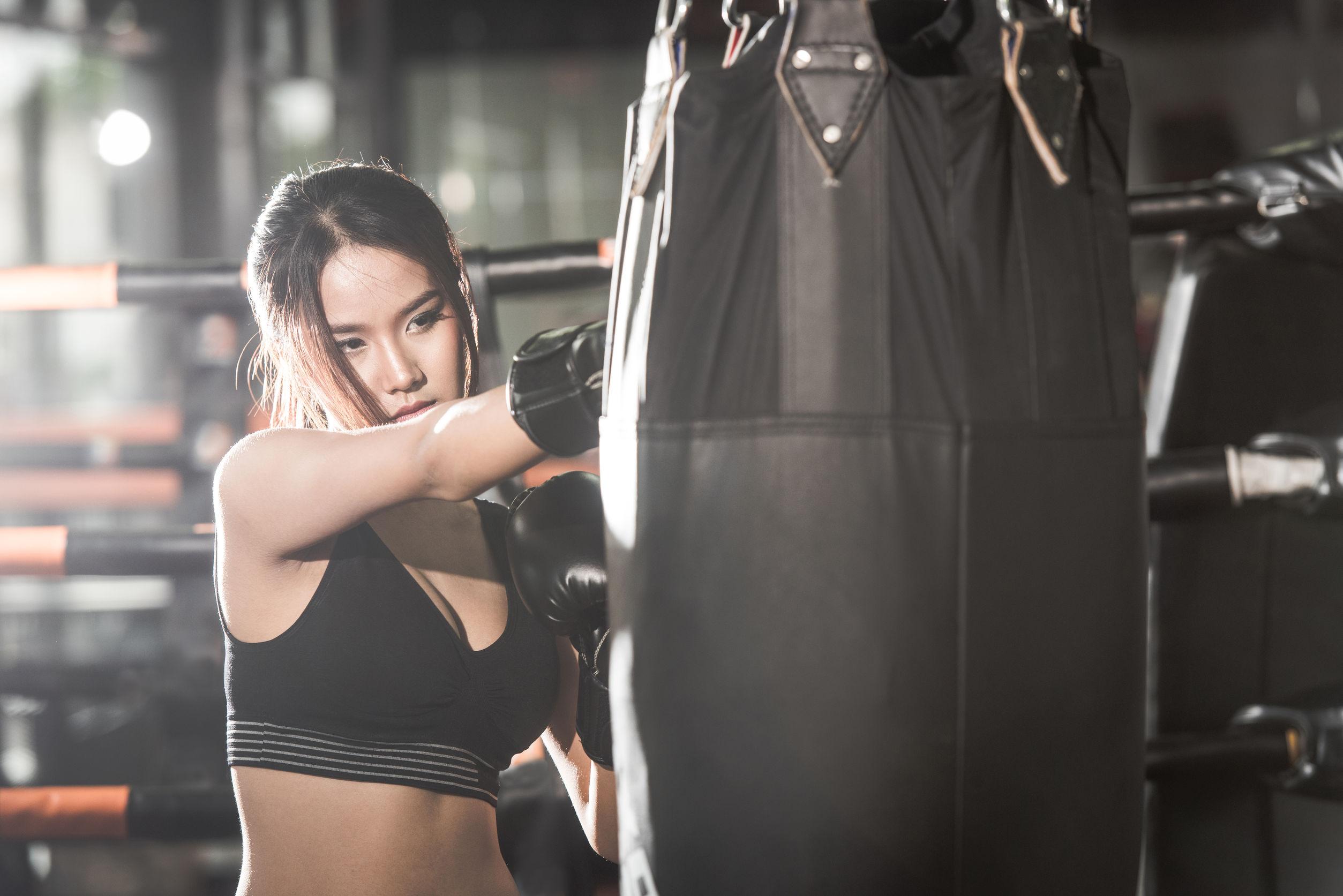 Linda mulher socando um saco com luvas de boxe na academia