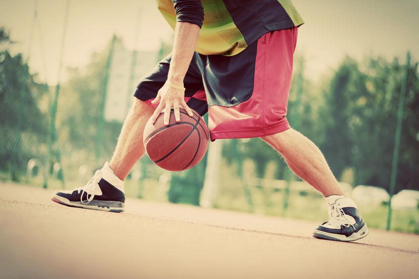 Hombre joven en la cancha de baloncesto regateando con la pelota. Estado de ánimo vintage