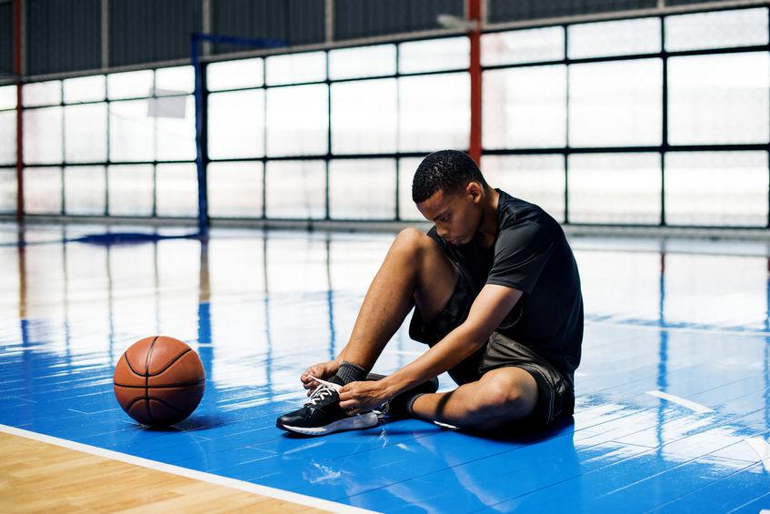Adolescente americano atando los cordones de sus zapatos en una cancha de baloncesto