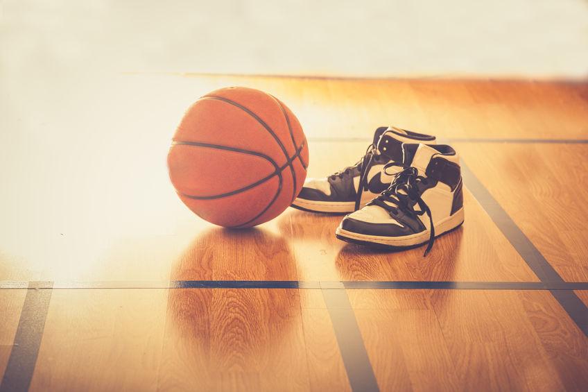 Cancha de baloncesto con pelota y zapatos.