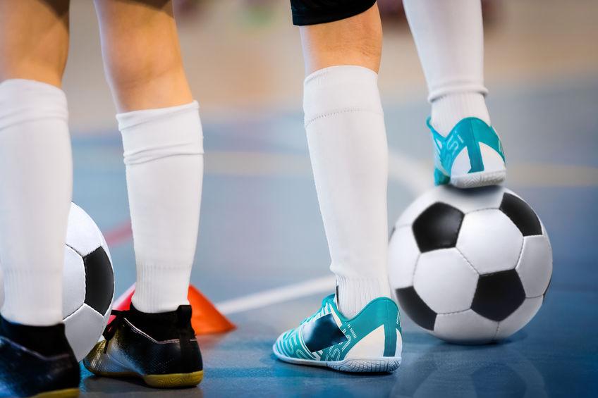 sosteniendo un balón de fútbol con el pie