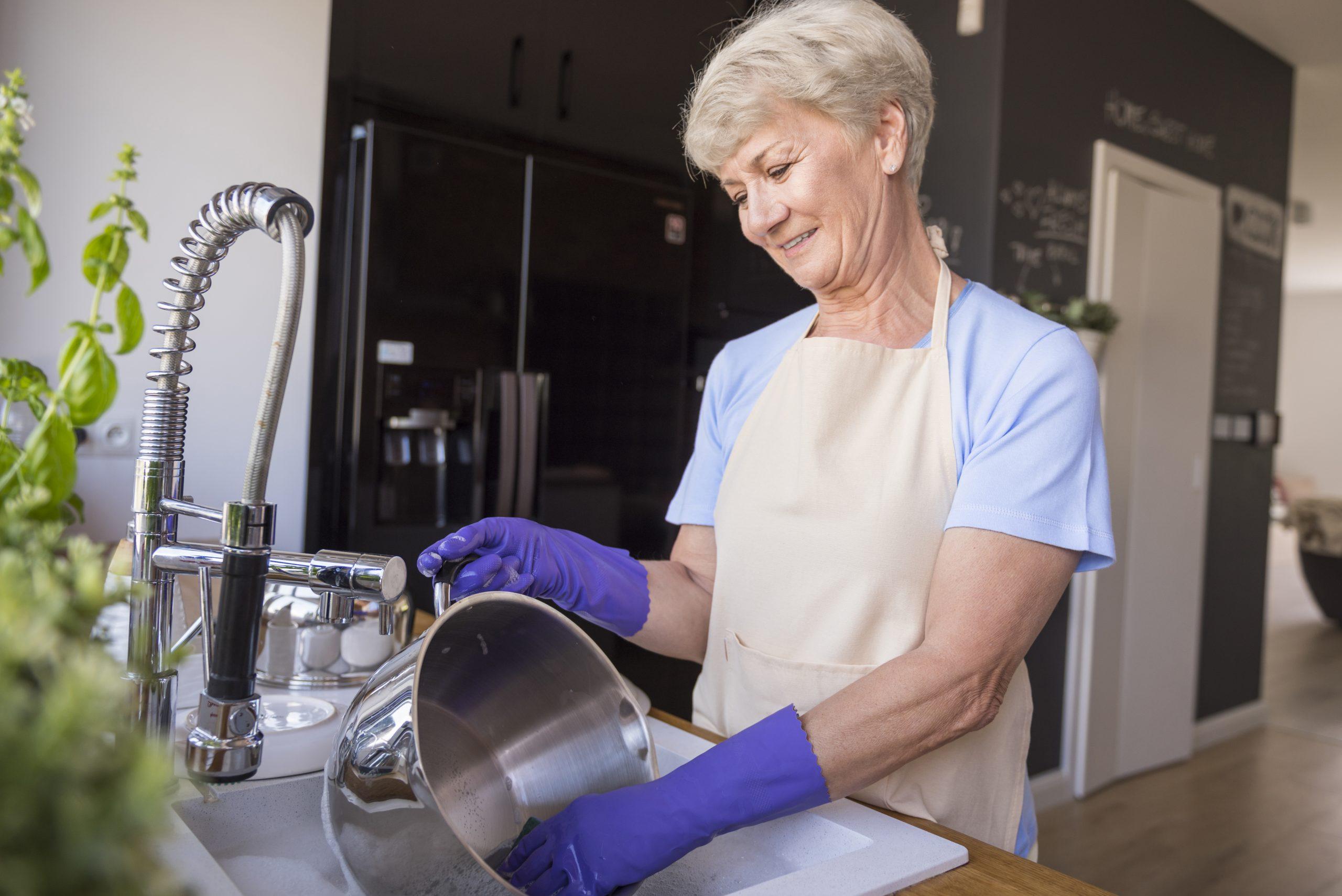 mujer mayor lavando freidora