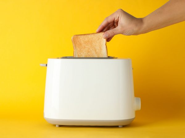 Female hand puts bread in a toaster on yellow background, space for text