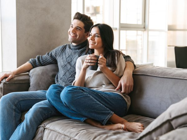 Happy young couple sitting on a couch at home, watching TV, drinking tea