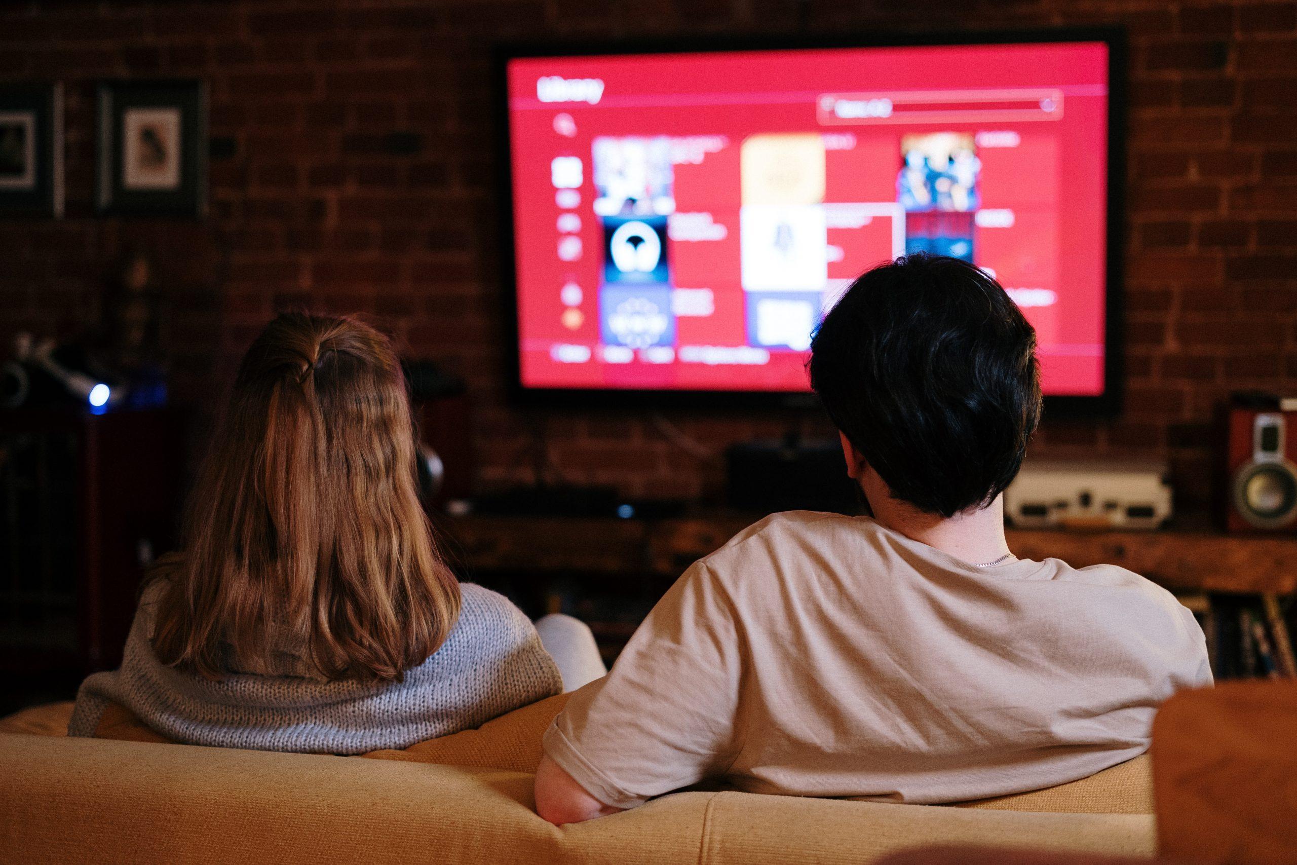 una pareja mirando televisión en la sala