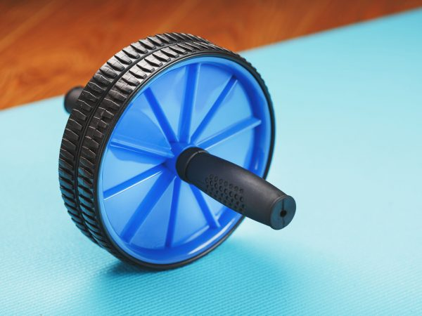 Blue roller for abs pumping classes on a blue fitness Mat. Athletic activity