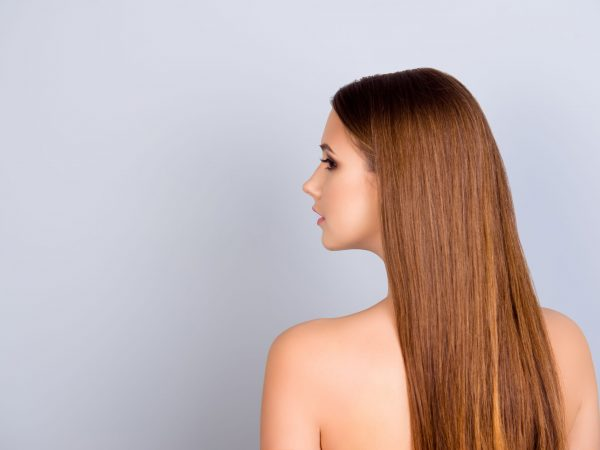 Health and beauty harmony and care advertising. Half face cropped portrait of young attractive lady with brown hair and smooth skin