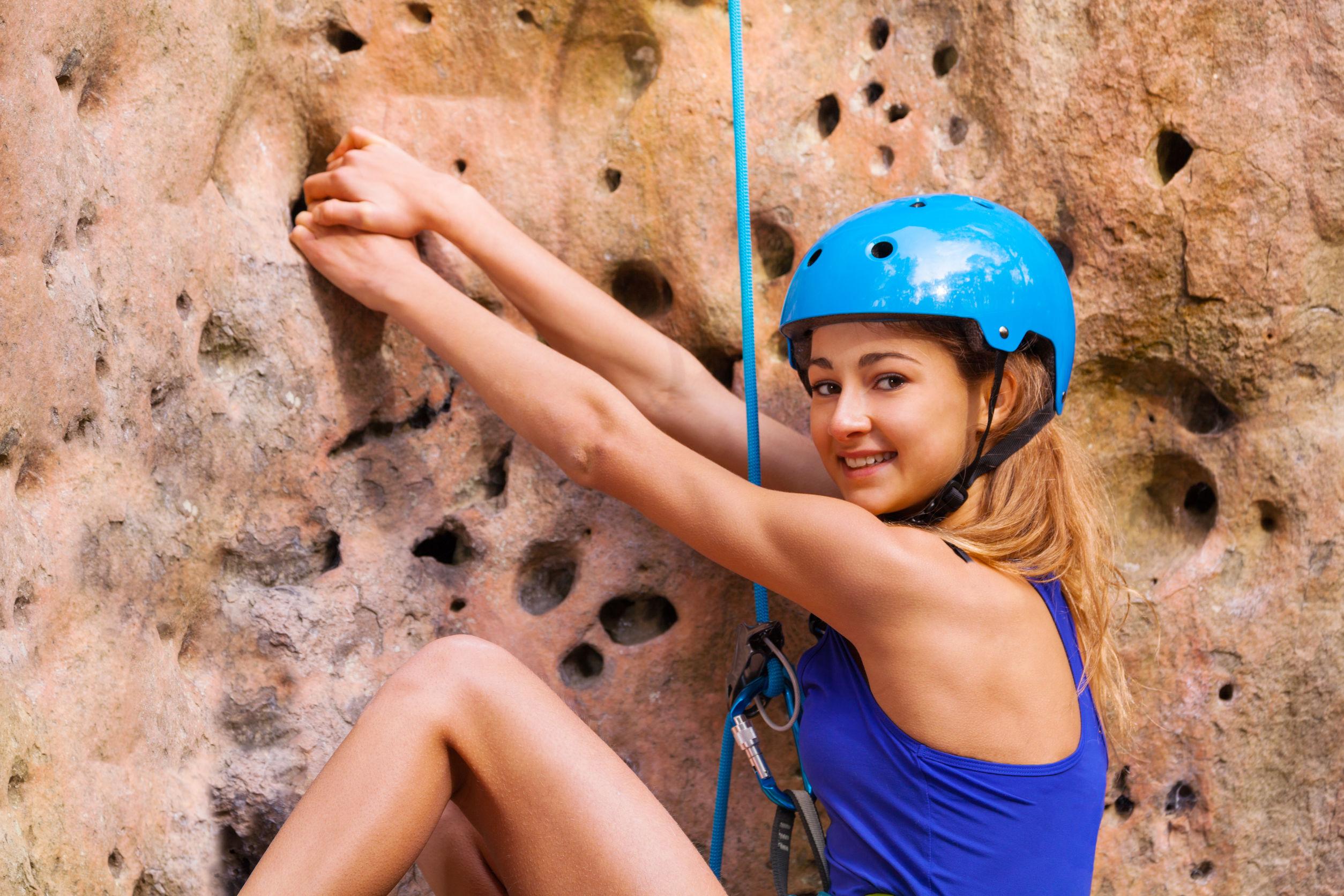 Mujer escaladora con casco haciendo ejercicio al aire libre
