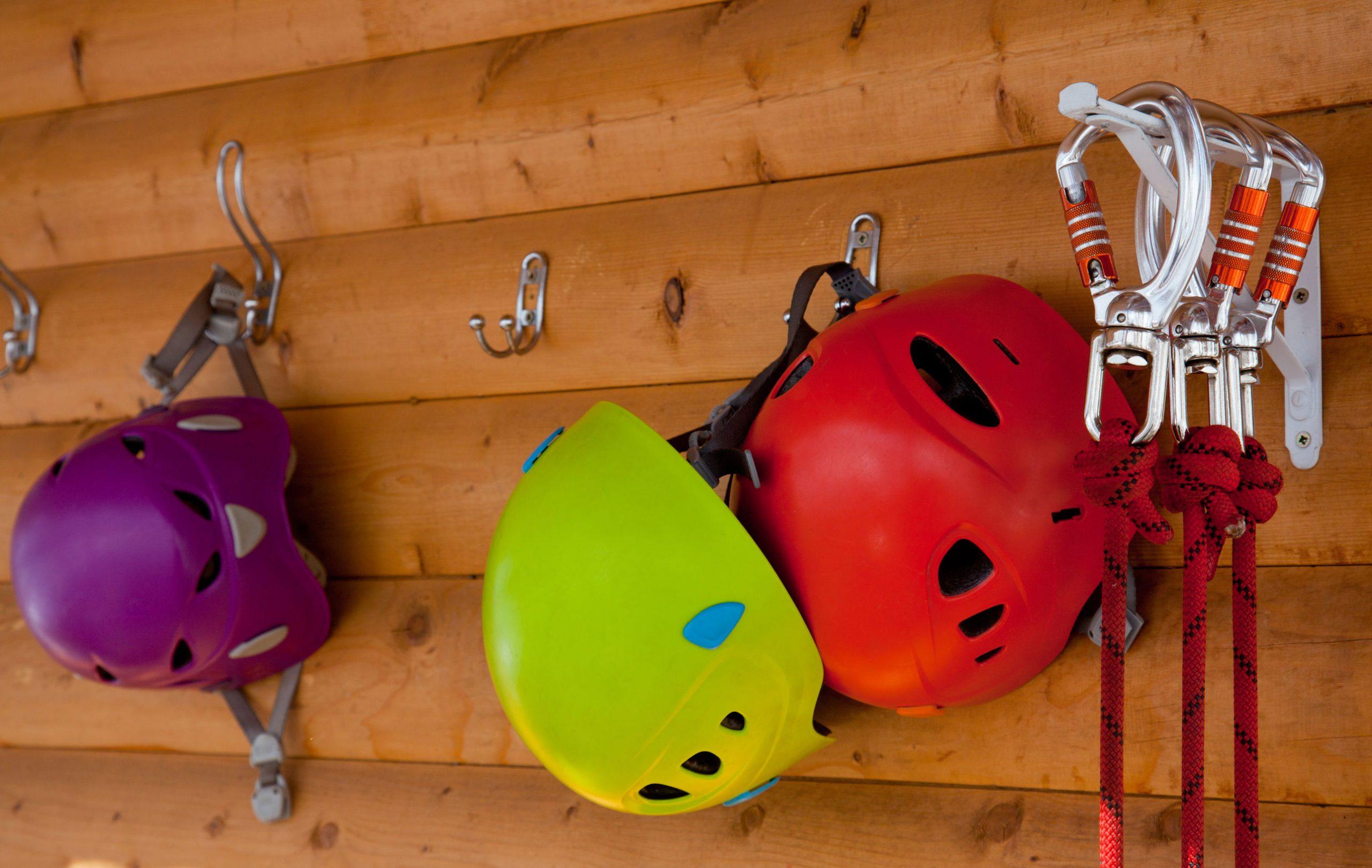 Cascos y arneses con mosquetones colgados en la pared de madera.