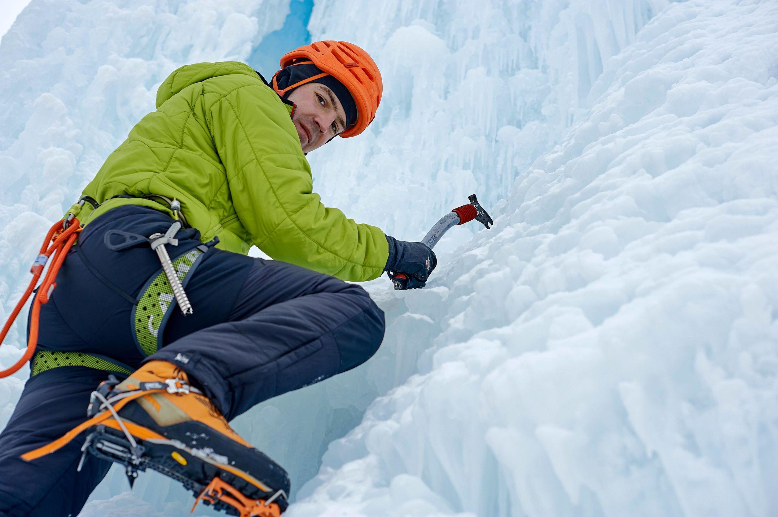 Hombre alpinista con hacha de herramientas para hielo en casco naranja escalando una gran pared de hielo.