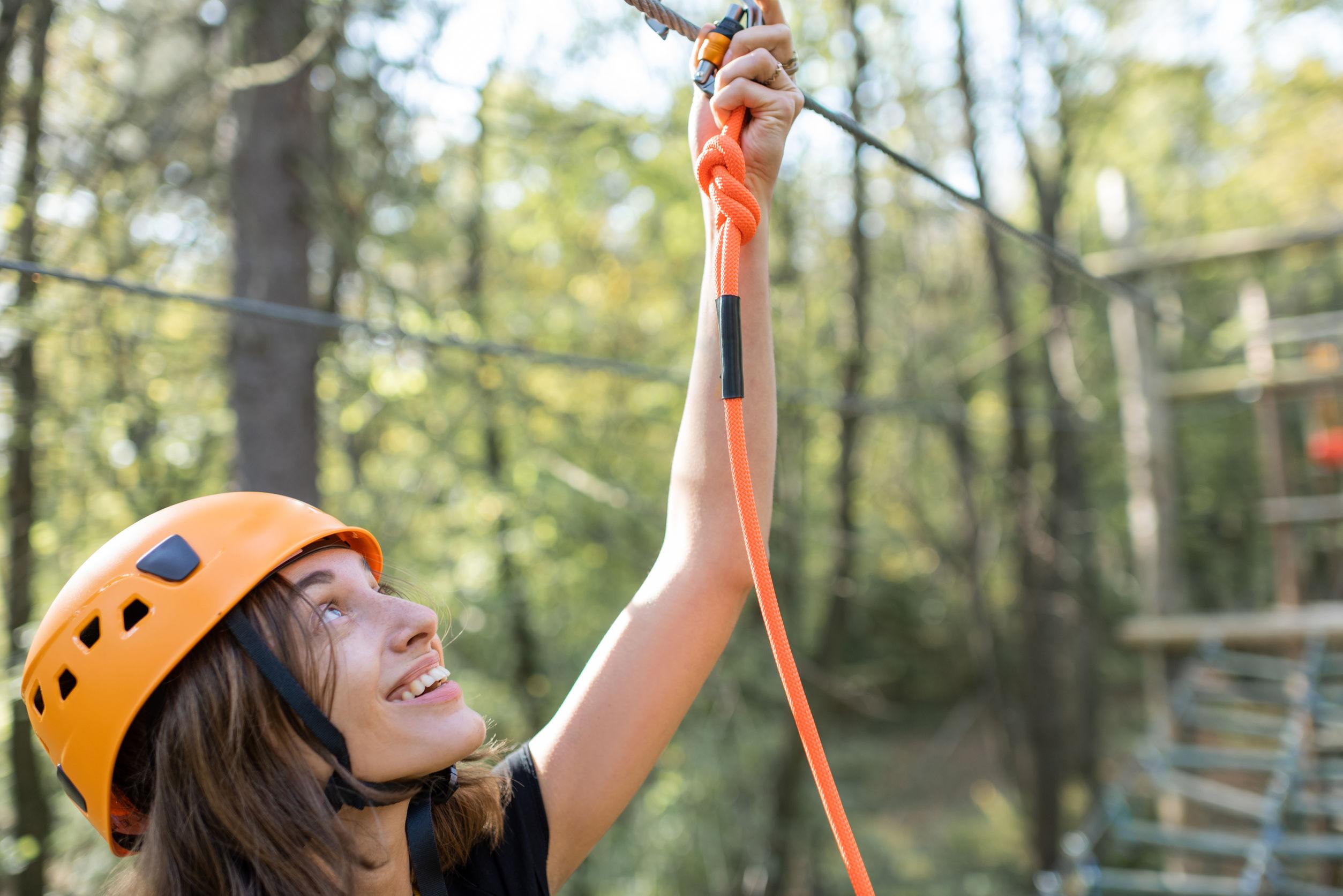 Retrato de una joven mujer bien equipada con una recreación activa en un parque de cuerdas