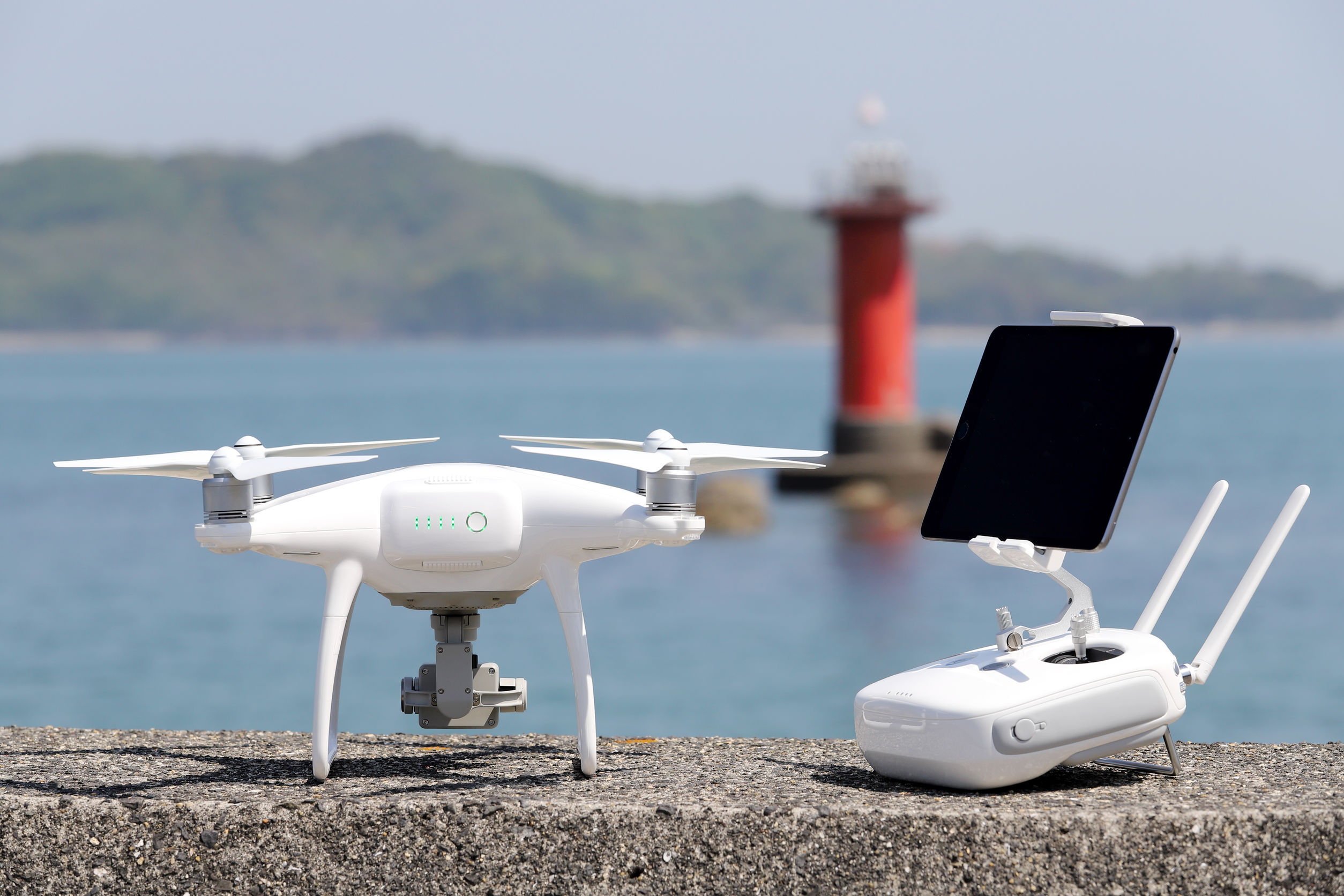 Drone y control remoto con monitor en embarcadero de hormigón