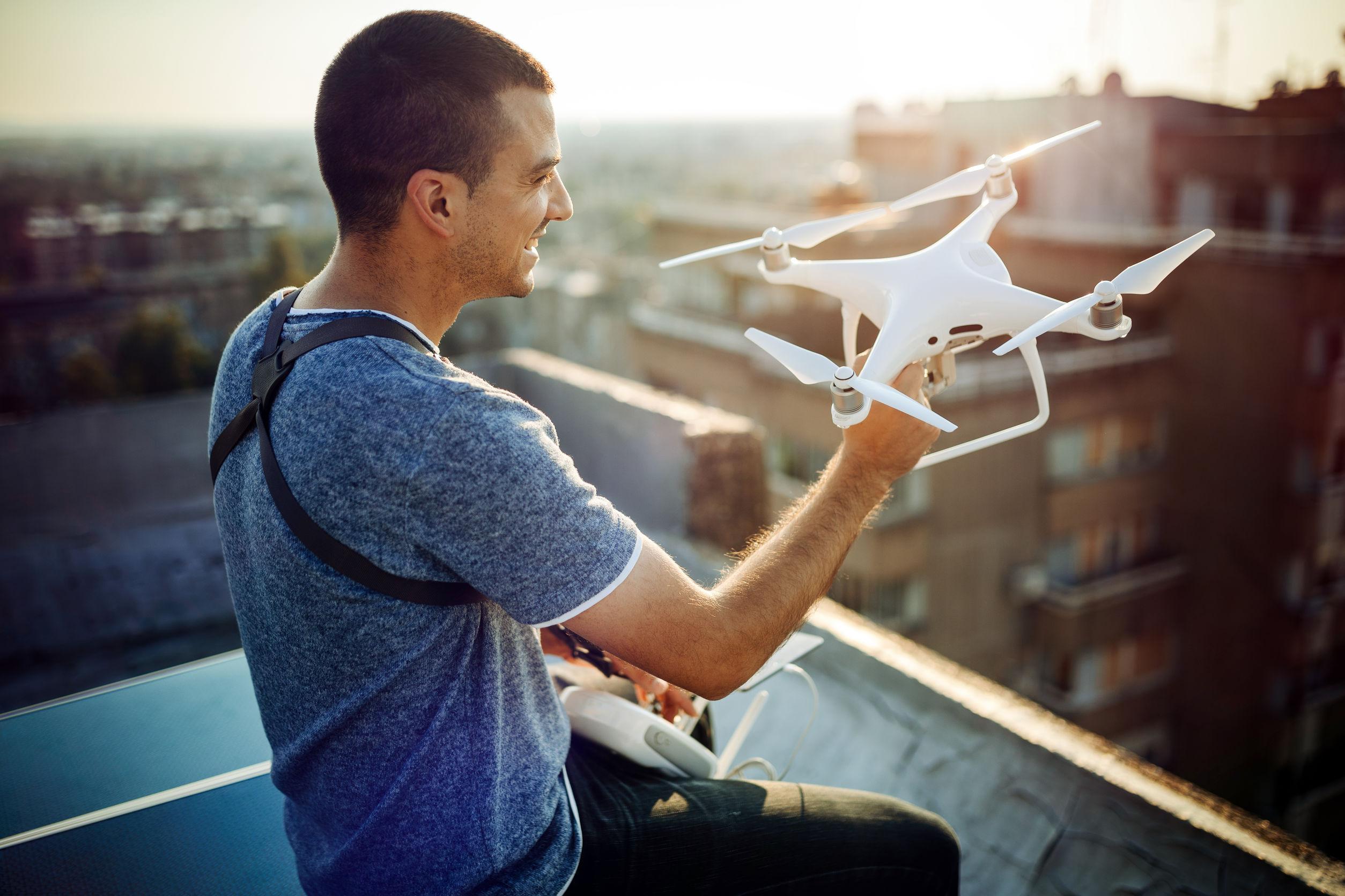 Hombre con drone en mano preparándose para ponerlo al vuelo