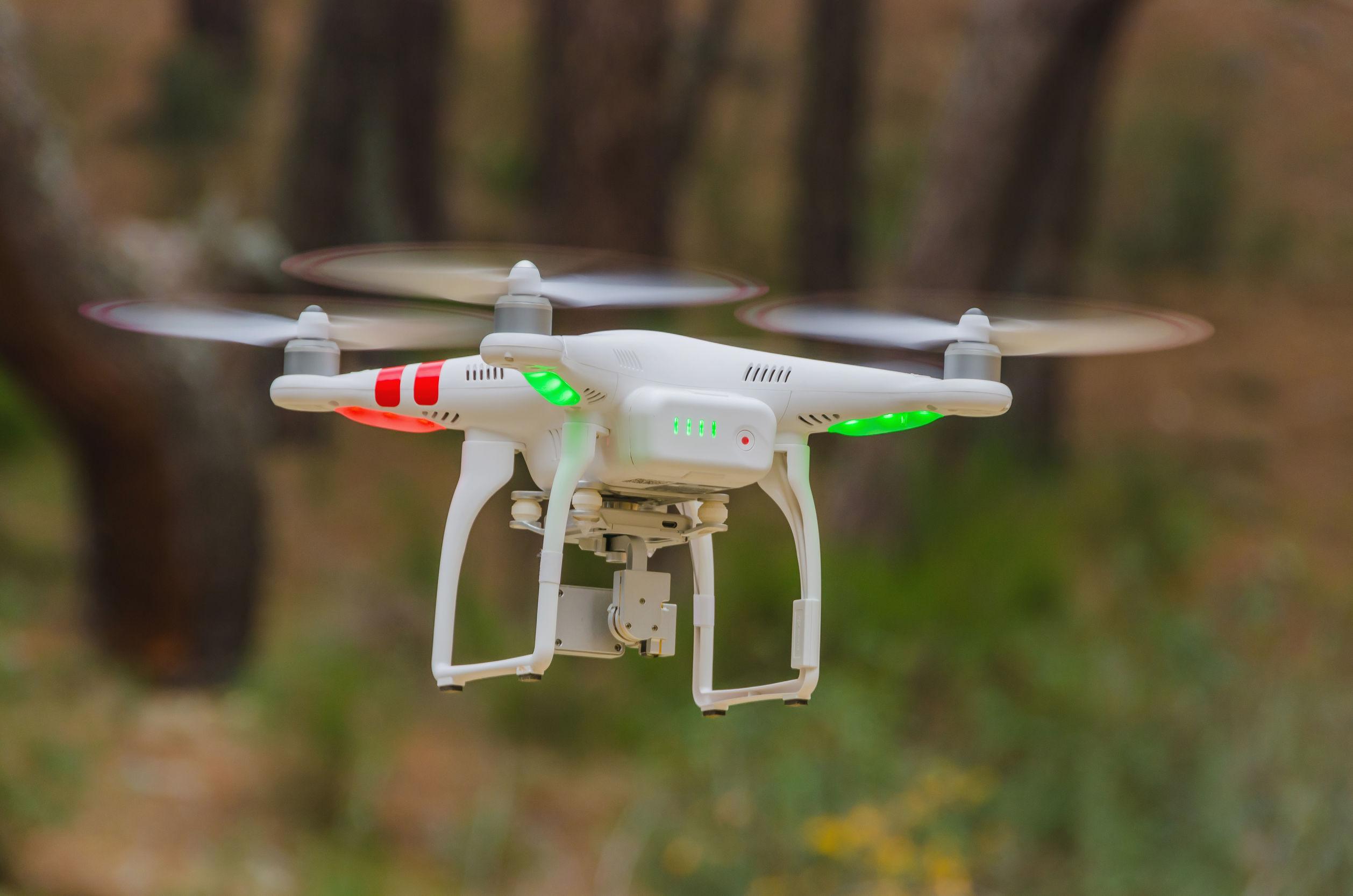 Un drone equipado con cuatro rotores y una cámara volando y toma de fotografías