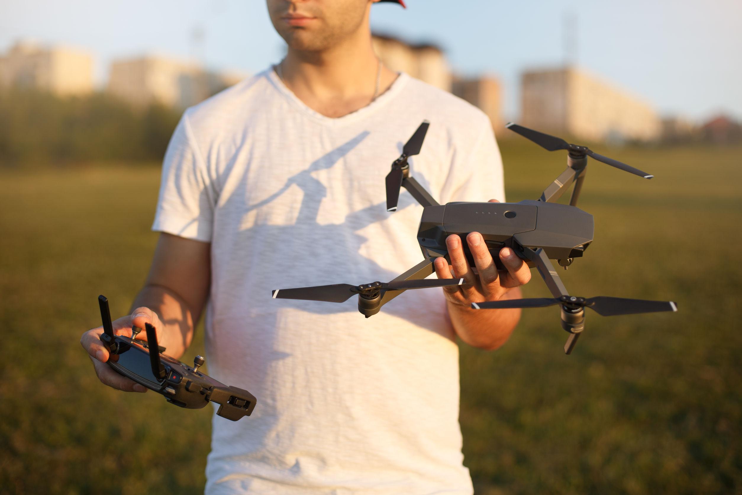 Hombre feliz muestra pequeño drone compacto y control remoto