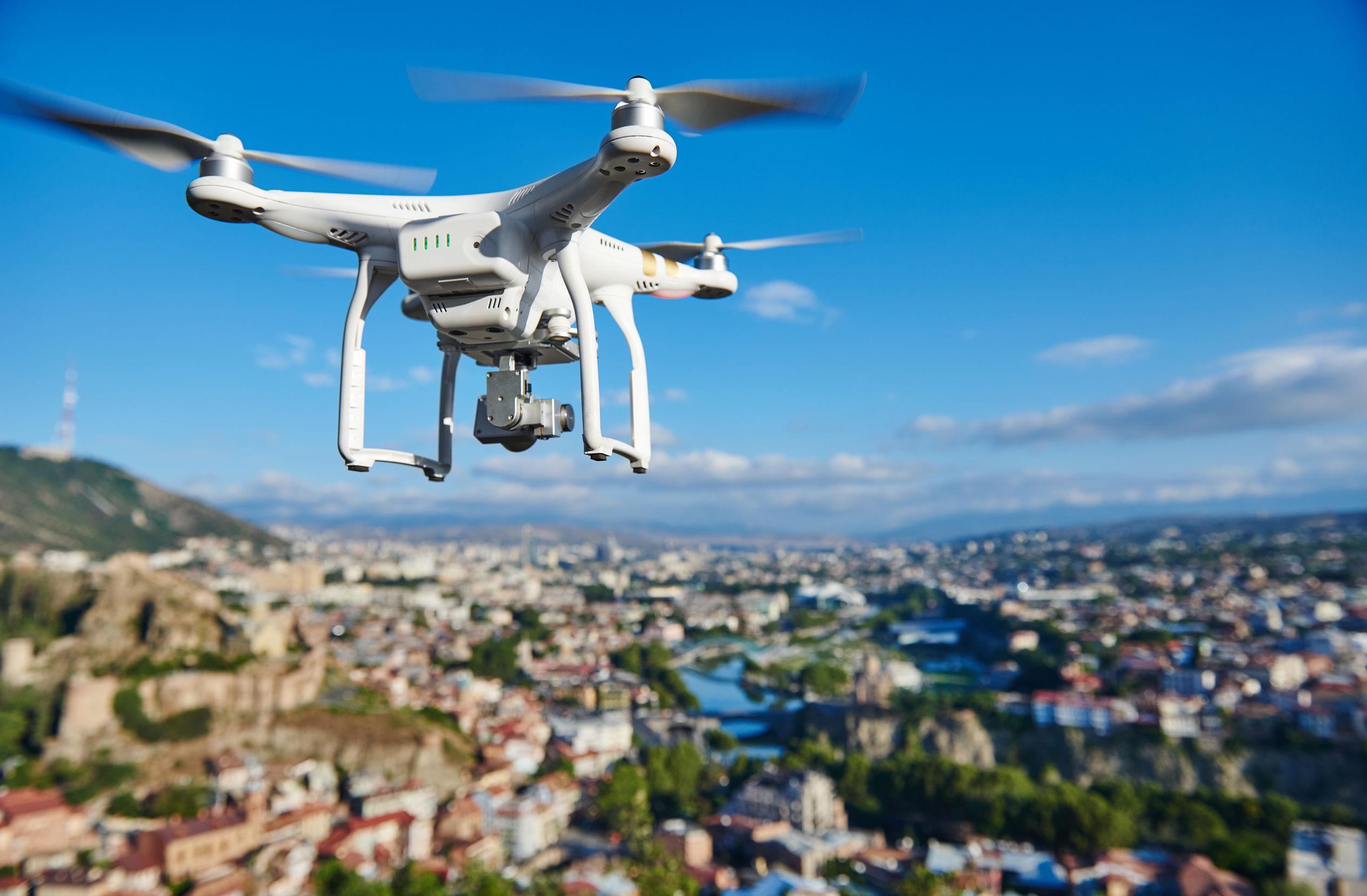 Drone blanco sobrevolando una ciudad