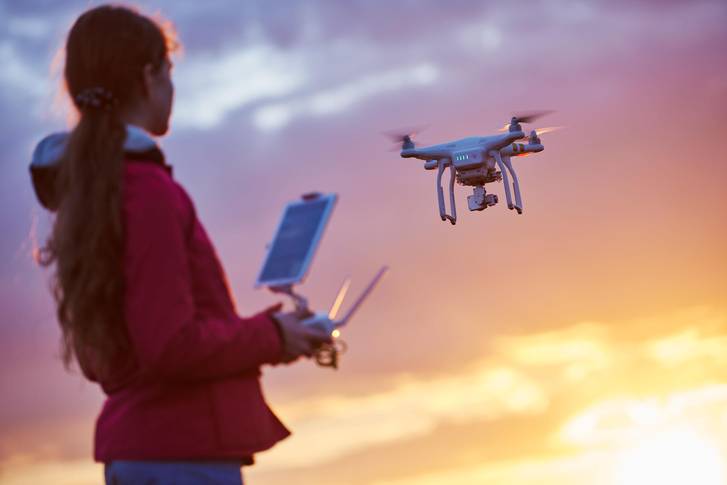 Drone volando o flotando por debajo de operación de control remoto en la puesta del sol