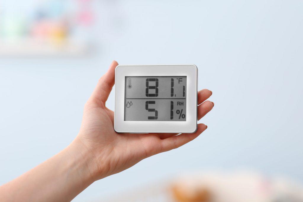 Mujer comprobando la temperatura y la humedad en la habitación del bebé