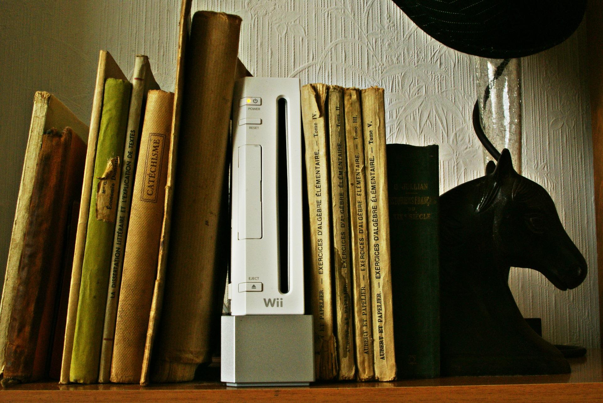 Consola de Nintendo Wii en estante entre a libros