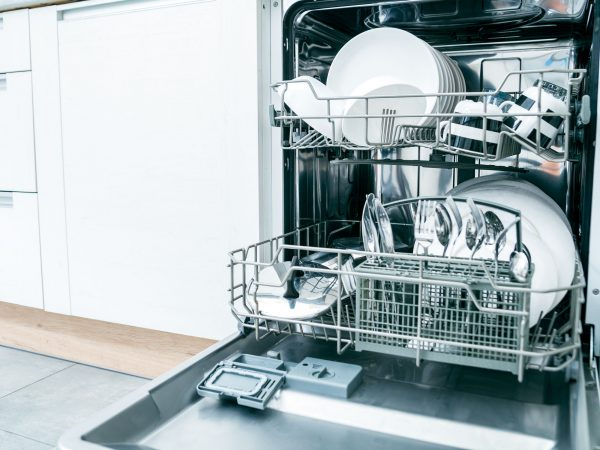 Open dishwasher with clean dishes in the white kitchen