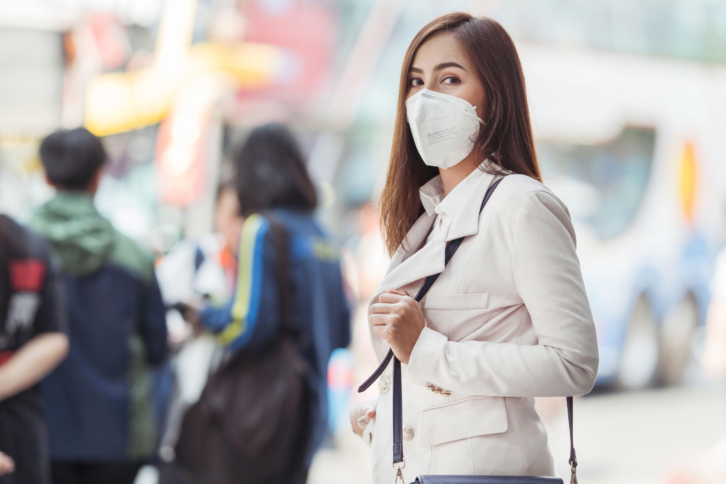 Una mujer asiática va a trabajar lleva una máscara N95.