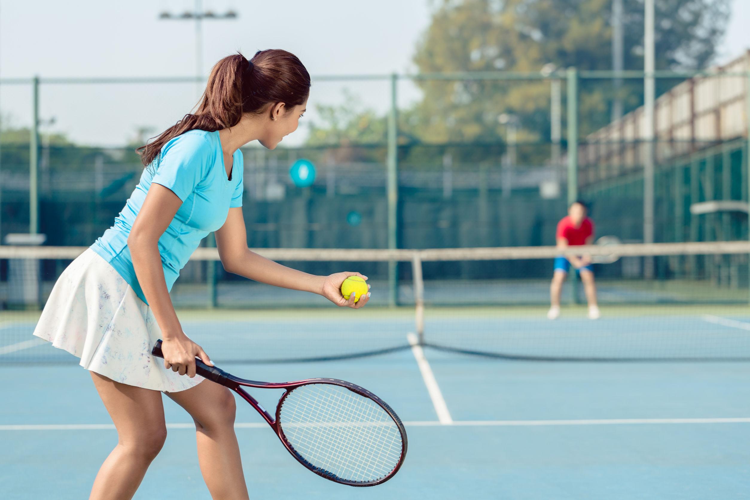Jugadora profesional sonriendo mientras sirve durante el partido de tenis