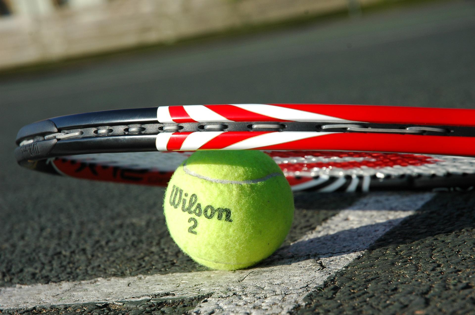 Pelota de tenis y raqueta en asfalto
