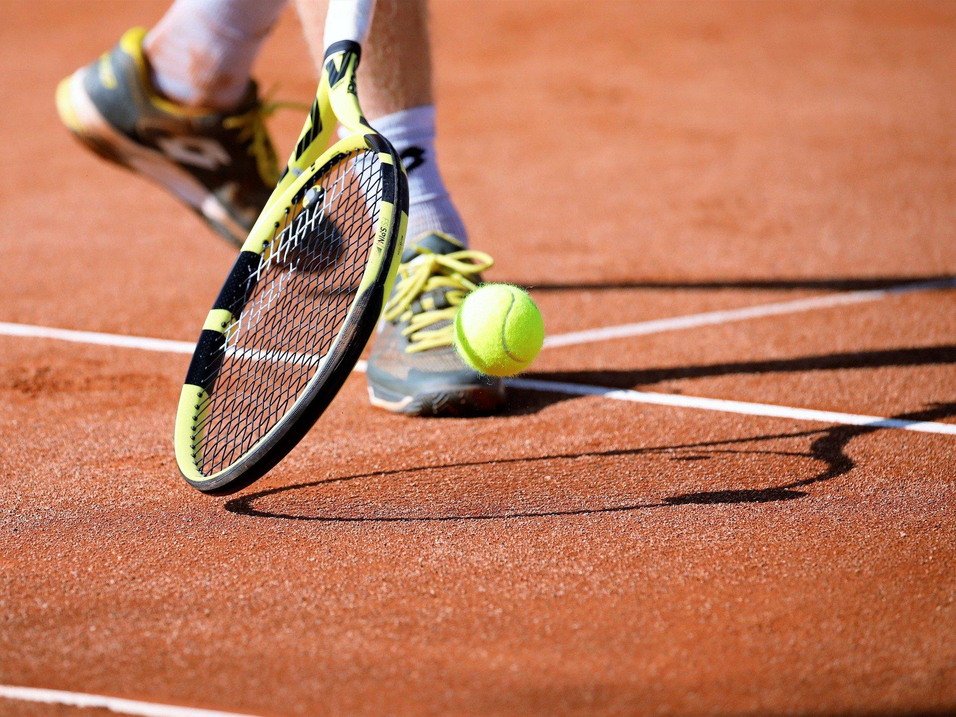 Persona golpeando pelota de tenis con raqueta