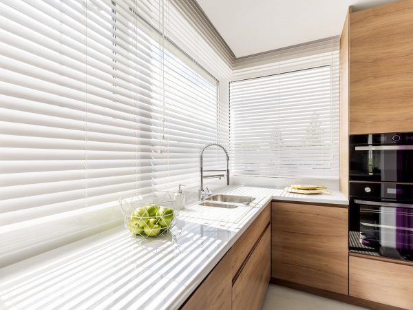 Modern bright kitchen interior with white horizontal window blinds, wooden cabinets with white countertop and household appliances