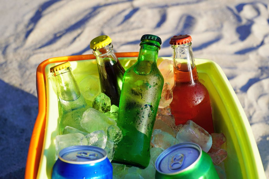 Puikūs gėrimai ir ledo kubeliai užpildyti šaltoje dėžėje ant paplūdimio smėlio.