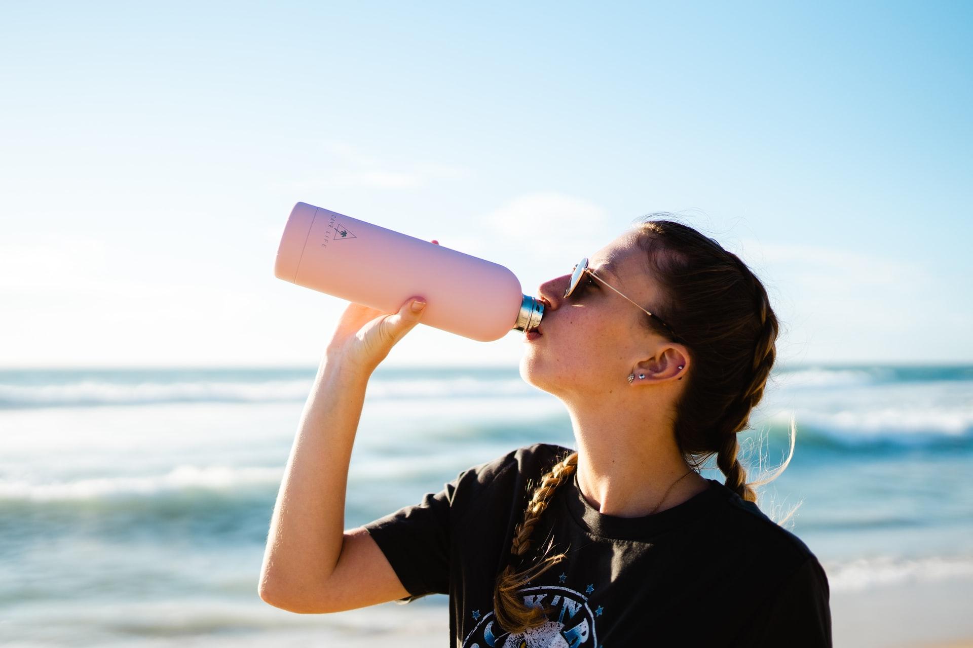 chica en la playa tomando agua