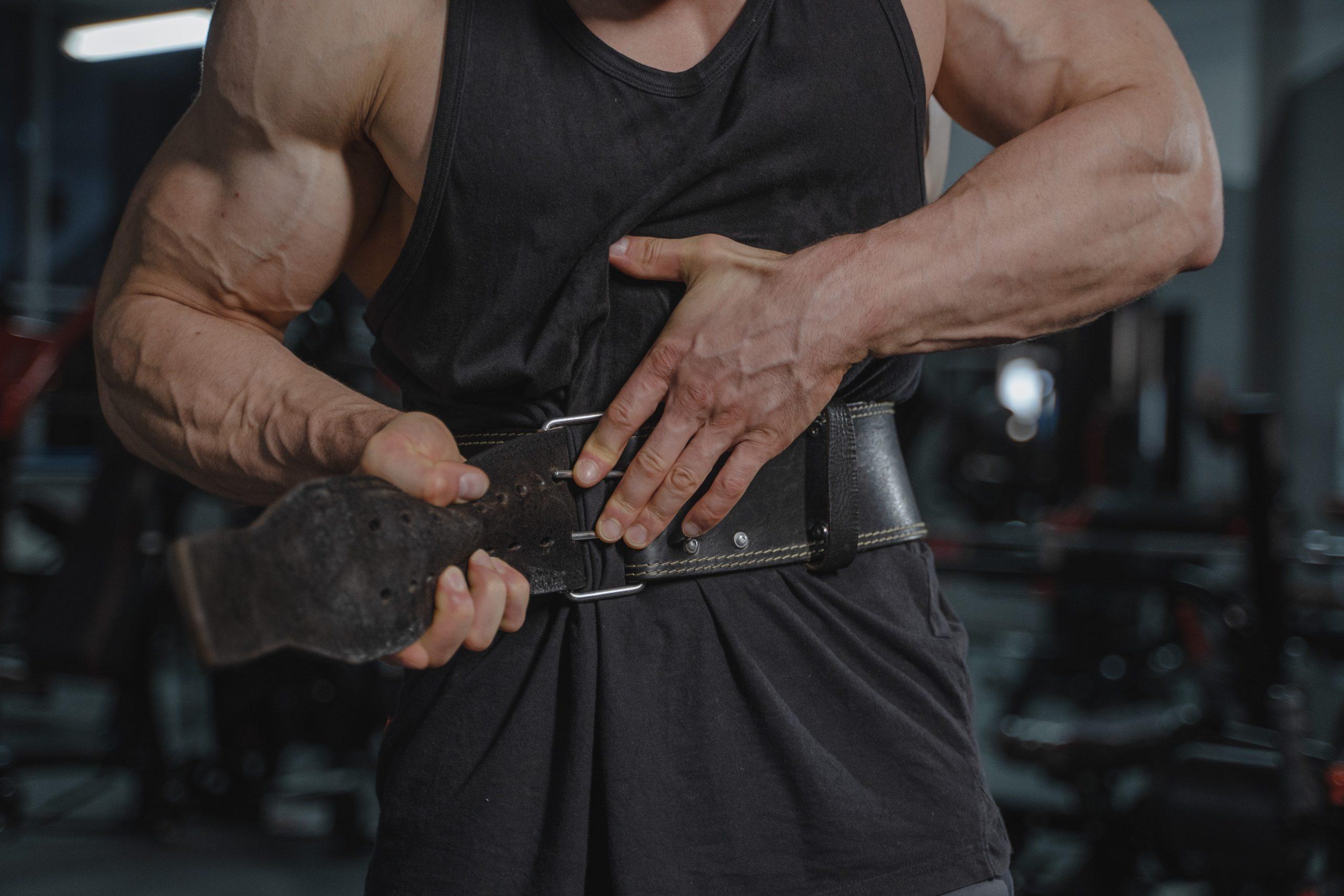 Hombre musculoso colocandose cinturon de levantamiento de pesas