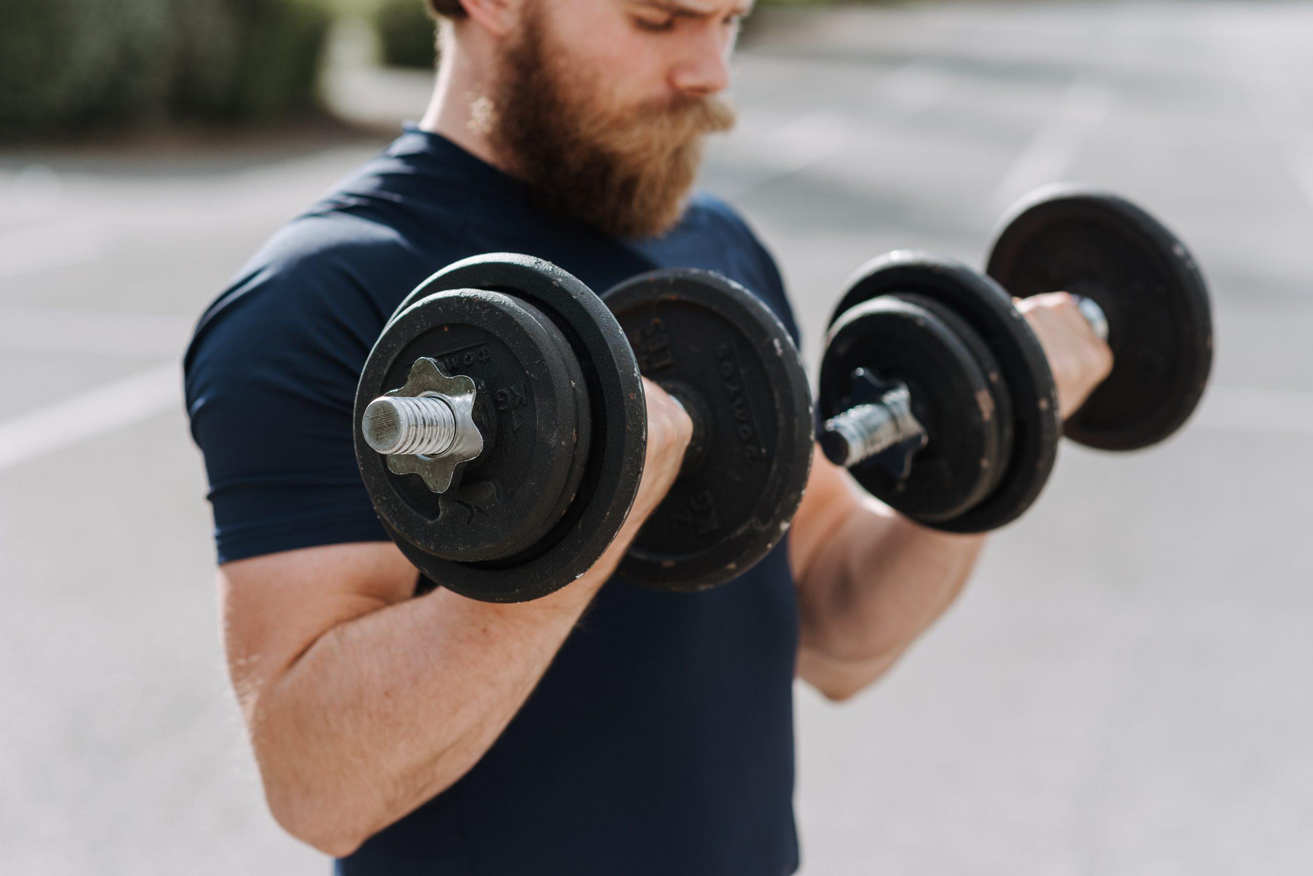Hombre ejercitando sus bíceps con mancuernas
